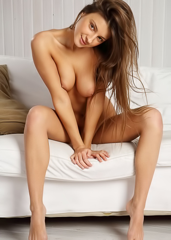 Tanned brunette shows off her sexy tan lines on white couch